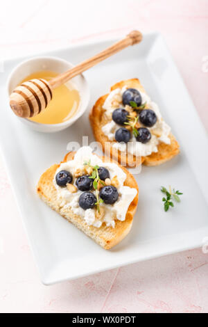 Toast with fresh berries blueberry Ricotta cheese, thyme, honey and hazelnuts, served - Stock Photo