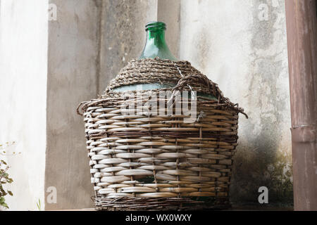 Empty carboy in rustic house - Stock Photo