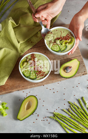 vegan dessert with asparagus, cucumber, avocado and flexseeds in a woman hands on a stone background - Stock Photo