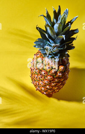 Ripe whole pineapple on a yellow paper background. Tropical Fruit. Top view - Stock Photo