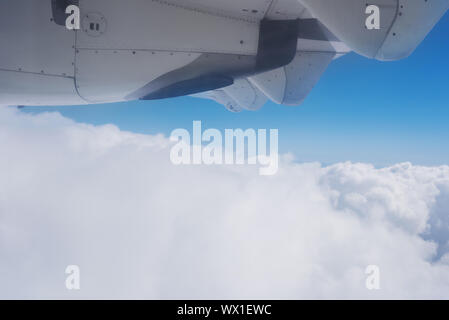 View of the clouds and the ocean from the airplane window. - Stock Photo