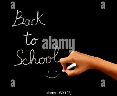 Handwriting phrase 'back to school' on blackboard in classroom, conceptual image of school time, teacher arm holding chalk and writing word, education - Stock Photo