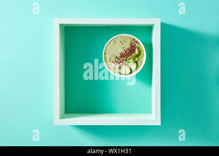 Healthy smoothie from green vegetables and fruits with flax seeds in a white bowl in square frame on a green background. Copy sp - Stock Photo