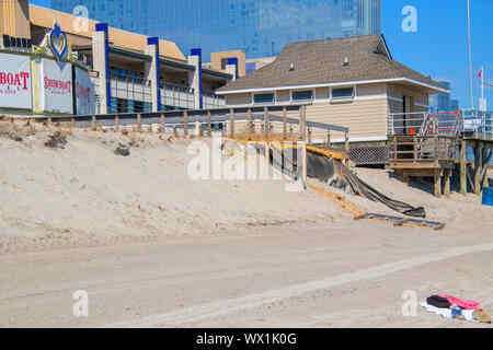 Atlantic City, New Jersey - September 9, 2019: Erosion of the sand of the beach with destruction of a asphalt path is seen in front of an Atlantic Cit - Stock Photo