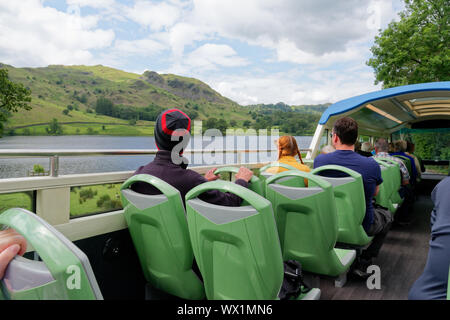 Tourists on an open top double decker bus passing Rydal Water in the lake District, Cumbria, UK - Stock Photo