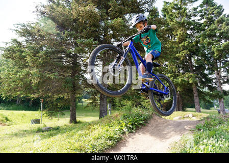 A seven year old boy doing jumps on his mountain bike
