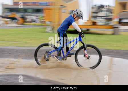 A young boy (7 yr old) riding his bike through a puddle - Stock Photo