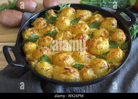 Young potatoes with cottage cheese are baked in the oven. - Stock Photo