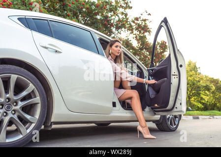Beautiful girl in summer in city, getting out of car, business class taxi, VIP car rental, pink suit, high-heeled shoes. Autumn and spring background - Stock Photo