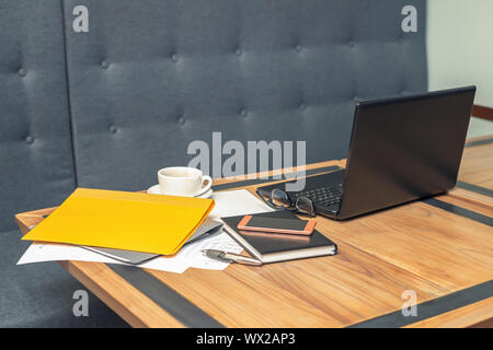 side view of glasses, smartphone, laptop, notebook and pen on the wooden table at office, selective focus office table, business concept - Stock Photo