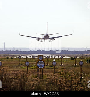 Airplane on landing, cross wind tunnel with runway position lights, Koeln-Bonn Airport, Germany - Stock Photo