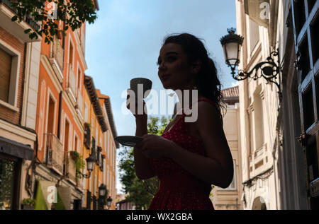 Beautiful young woman enjoying coffe cup and looking at street of European old town at morning time. Having break or breakfast. - Stock Photo