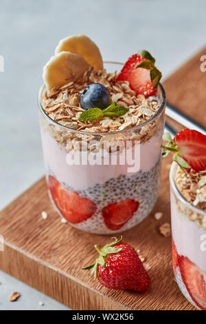 Glass of fruit smoothie and fresh berries with oat homemade granola, chia seeds on a wooden board on a gray. - Stock Photo