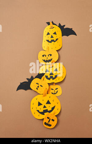 Different handcraft scary pumpkins and bats on a brown background with space for text. Creative composition for Halloween. Flat - Stock Photo