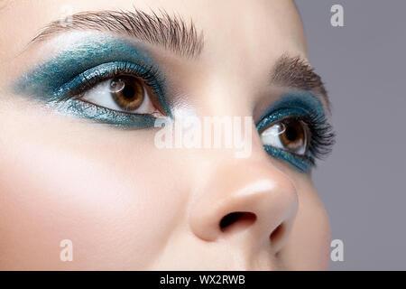 Closeup macro shot of human female eye. Girl with perfect skin and blue-green smoky eyes eye shadows - Stock Photo