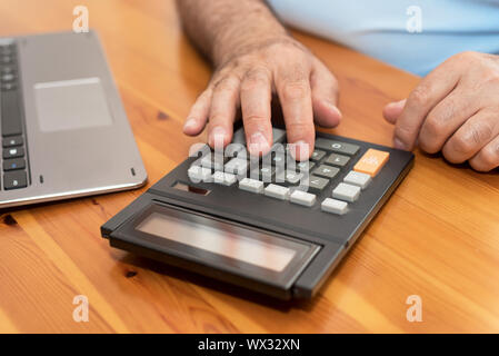 Man using calculator, calculating bills at home. - Stock Photo