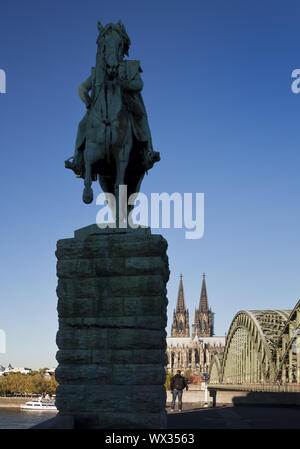 Equestrian statue of Emperor Wilhelm I with Cathedral and Hohenzollernbruecke, Cologne - Stock Photo