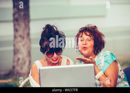Two happy senior women - friends sitting in a cafe sending a kiss online during a video call with a laptop.