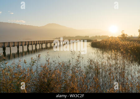 long wooden boardwalk pier over water in golden evening light with a mountain landscape silhouette i - Stock Photo