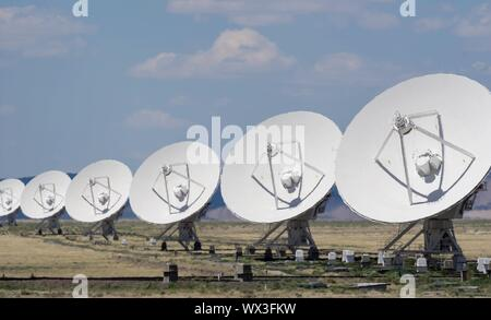 many white satellite dishes all in a row in the shimmering desert heat - Stock Photo