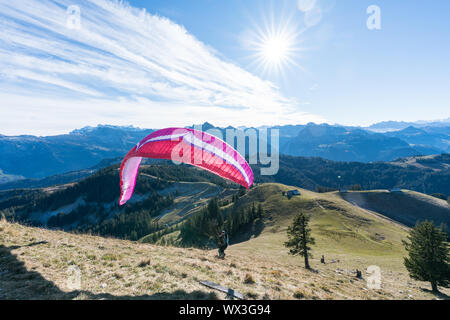 Einsiedeln, SZ / Switzerland - November 25, 2018: man with paraglider preparing for take off from a - Stock Photo