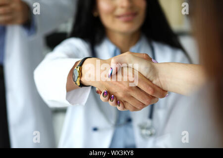Arm of female GP shaking hands with visitor - Stock Photo