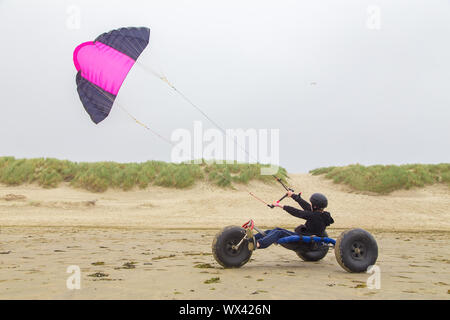 Teenage boy drives buggy with kite on beach - Stock Photo