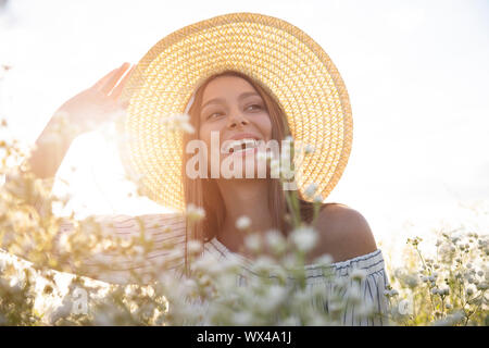 Beautiful brown-haired woman in white adjusting her hat sitting among field flowers - Stock Photo
