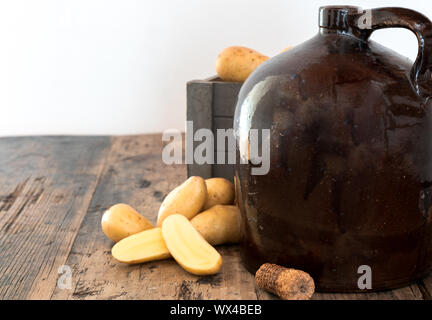 vintage moonshine jug on a rustic wooden table with potatoes and corn cob cork - Stock Photo