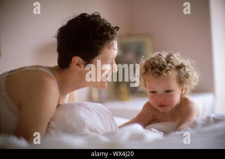 A mother and son sharing a tender moment on a bed. - Stock Photo