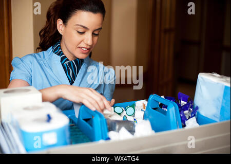 Pretty female housekeeper busy working. Checking and arranging all toiletries in cart - Stock Photo