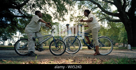 Mid-adult mother and her son sitting on bicycles and talking in an outdoor park. - Stock Photo