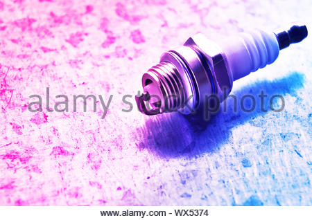 New spark plug for internal combustion engine on toned metal background. Space for text - Stock Photo