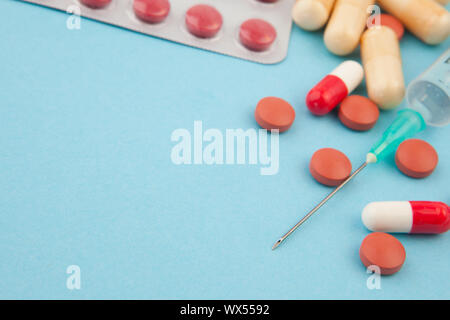 Syringe and spills against a blue background - Stock Photo