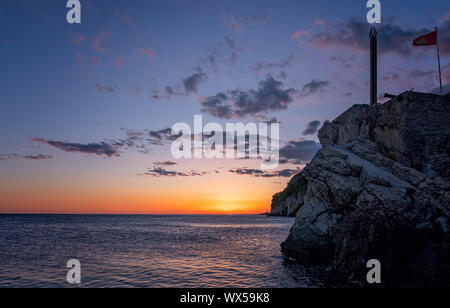 Obelisk and flag on the cliffs at dusk - Stock Photo