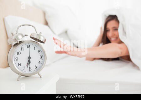 The woman reaches out to silence her alarm from under the quilt. - Stock Photo