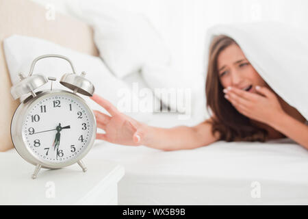 A woman is reaching out to silence her alarm clock while underneath her blanket in bed. - Stock Photo