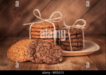 Various shortbread, oat cookies, chocolate chip biscuit on dark rustic wooden table. - Stock Photo