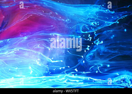 Blue and purple paints and inks swirling together in water abstract background
