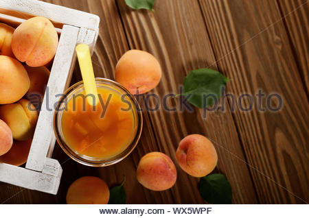 Apricot smoothie in mason jar and crate on wooden table. Top view - Stock Photo