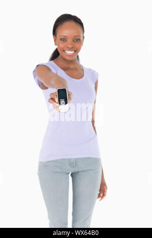 Close up of phone being presented by smiling woman on white background - Stock Photo