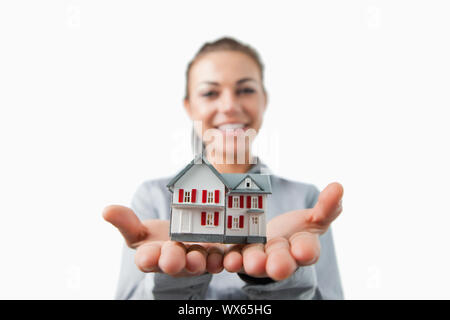 Miniature house being presented by female estate agent against a white background - Stock Photo