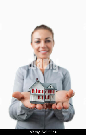 Miniature house being presented by young female estate agent against a white background - Stock Photo