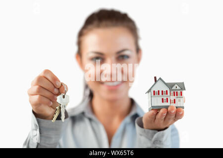 Keys and miniature house being presented by female estate agent against a white background - Stock Photo