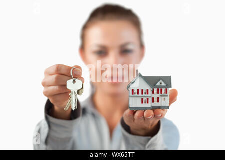 Miniature house and keys being presented by female estate agent against a white background - Stock Photo