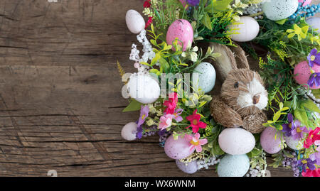 easter wreath with colorful eggs and flowers and a rabbit in the center - Stock Photo