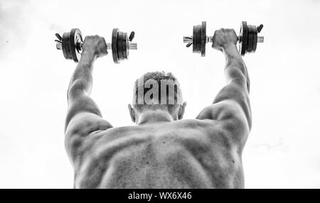 Sport equipment. Bodybuilding sport. Sport lifestyle. Dumbbell exercise gym. Muscular man exercising with dumbbell rear view. Pain is temporary, pride is forever. Sportsman with strong back and arms. - Stock Photo