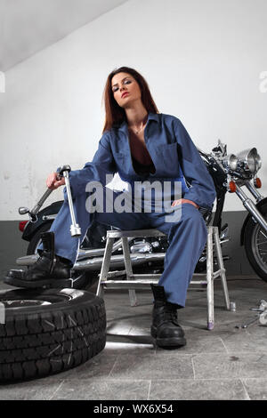 Photo of a beautiful female mechanic working on a motorcycle wearing overalls and holding a large ratchet. - Stock Photo
