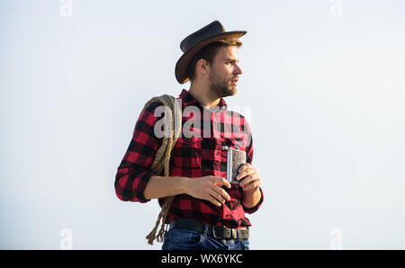 Hero of western culture. Farmer drink water metal flask. Looking for adventures. Farmer cowboy handsome man relaxing after hard working day at ranch. Lonely farmer sky background. Rustic style. - Stock Photo