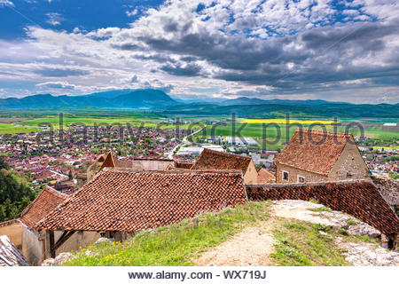 Spring view over the Rasnov city, in Brasov county (Romania), with old houses of the Rasnov citadel in the foreground and Piatra - Stock Photo